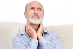 Sore throat man. Elderly man sitting suffering from throat problems royalty free stock photo