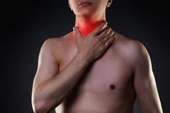 Sore throat, men with pain in neck, black background. Sore throat, man with pain in neck, black background, studio shot stock photos