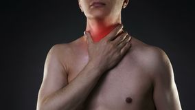 Sore throat, men with pain in neck, black background. Studio shot stock footage