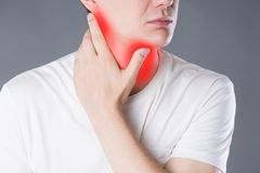 Sore throat, men with pain in neck, studio shot on gray background. Sore throat, man with pain in neck, studio shot on gray background, painful area highlighted royalty free stock image