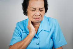 Sore throat senior woman. On gray background stock photo