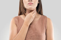 Sore throat woman on gray background. Sore throat of a women. Touching the neck. Isolated on white background stock image