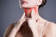 Sore throat, woman with pain in neck, gray background. Studio shot stock image