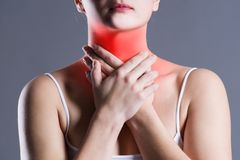 Sore throat, woman with pain in neck, gray background. Studio shot stock images