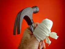 Sore Thumb with Hammer. Close-up of a man's hand with the thumb wrapped in a huge bandage, and holding a hammer that could have done the damage Royalty Free Stock Image
