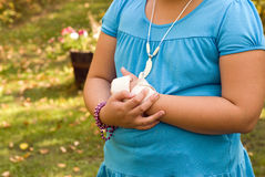 Sore Wrist. Young girl holding her sore wrist with a sloppy bandage on it stock photos