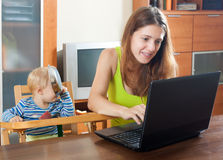 Sorehead mother with baby using laptop Stock Image