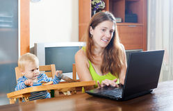 Sorehead mother with baby using laptop Stock Images