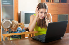 Sorehead mother with baby using laptop. Whiner mother with baby using a laptop at a table in the house Royalty Free Stock Images