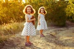 Sorella bambini che restano sulla strada in un parco ad una passeggiata nel sole del sole di sera Ragazze delle sorelle di amiciz Fotografie Stock Libere da Diritti