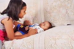 Sorella che gioca con il fratello del bambino che dorme sul sofà, Pune, maharashtra fotografie stock libere da diritti