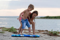 Sorella che insegna a suo fratello a come praticare il surfing Immagine Stock Libera da Diritti