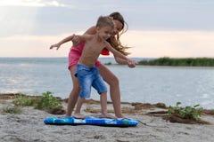 Sorella che insegna a suo fratello a come praticare il surfing Fotografie Stock Libere da Diritti
