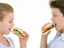 Sorella che mangia mela dal fratello che mangia cheeseburger Immagine Stock Libera da Diritti