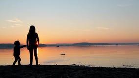 Sorella con un fratello piccolo alle pietre del tiro di tramonto al mare archivi video