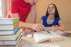 Sorella di spiegazione di esercizio del fratello più anziano che lavora allo scrittorio con la lezione di scrittura Immagine Stock
