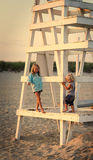 Sorella e fratello alla spiaggia durante il tramonto Fotografia Stock