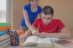 Sorella e fratello dello studente che studiano dentro, libri di lettura allo scrittorio in salone immagine stock