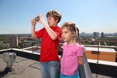 Sorella, fratello con la città della foto della macchina fotografica Immagini Stock