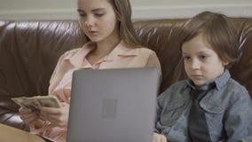Sorella più anziana e più giovane fratello piccolo che si siedono sul sofà di cuoio Il computer portatile della tenuta del ragazz video d archivio