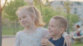 Sorella sorridente ed abbraccio divertente del fratello in parco lustro del sole Movimento lento archivi video