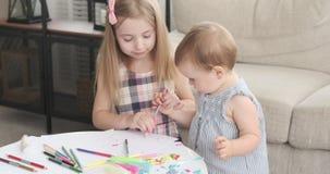 Sorelle che disegnano insieme alla matita di colore a casa stock footage