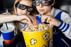Sorelle che mangiano popcorn nel teatro 3D Fotografie Stock Libere da Diritti