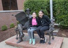 Sorelle che posano con il bronzo di Will Rogers su un banco, Claremore, Oklahoma Immagini Stock Libere da Diritti