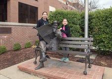 Sorelle che posano con il bronzo di Will Rogers su un banco, Claremore, Oklahoma Immagine Stock Libera da Diritti