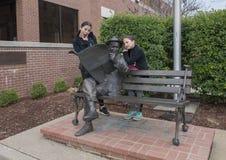 Sorelle che posano umoristico con il bronzo di Will Rogers su un banco, Claremore, Oklahoma Fotografie Stock