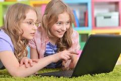 Sorelle degli adolescenti che per mezzo del computer portatile Fotografie Stock