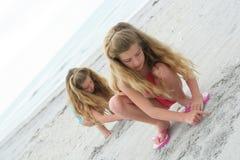 Sorelle gemellare che giocano nella sabbia immagine stock