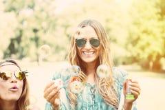 Sorelle gemellate che fanno le bolle di sapone in un parco Immagine Stock