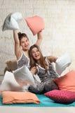 Sorelle gemellate con i cuscini nella camera da letto Fotografie Stock