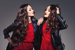Sorelle gemelli nella risata di stile dei pantaloni a vita bassa Due modelli di modo Wom Fotografia Stock