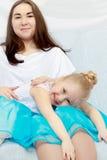 2 sorelle stanno sedendo sullo strato Fotografia Stock
