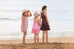 3 sorelle stanno sull'esame fronte mare indietro una persona sullo SH Fotografie Stock