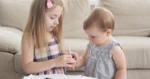 Sorelle sveglie che disegnano con la matita di colore a casa stock footage
