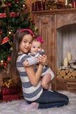 Sorelle sveglie che si siedono sul tappeto bianco vicino all'albero di Natale e camino, maglioni a strisce d'uso e fasce rosse So immagini stock