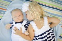 Sorellina Laying Next a suo fratello del bambino sulla coperta Immagini Stock