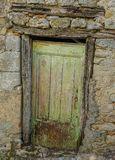Old door in a village. Soreze, Midi Pyrenees, France - August 5, 2017: Old and abandoned wooden door in a stone wall royalty free stock images