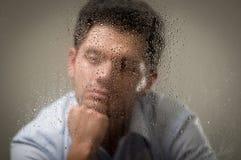 Sorge depresed den jungen Mann, der über seiner Hand, hinter einem unscharfen Fenster mit Tropfen, grauer Hintergrund aufwirft Lizenzfreies Stockbild