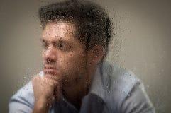 Sorge depresed jungen Mann, hinter einem unscharfen Fenster mit Tropfen, grauer Hintergrund Stockfoto