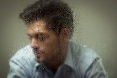 Sorge depresed jungen Mann, hinter einem unscharfen Fenster mit Tropfen, grauer Hintergrund Lizenzfreies Stockfoto