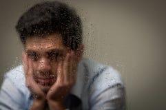 Sorge depresed jungen Mann mit beiden Händen in seinem Gesicht, hinter einem unscharfen Fenster mit Tropfen, grauer Hintergrund Stockbild