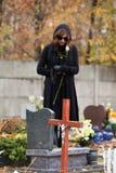 Sorgen machende Frau am Kirchhof im Herbst lizenzfreie stockfotografie