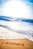 Sorgen Sie sich geschrieben in den Sand auf einen Strand Lizenzfreies Stockbild