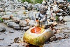 Sorgente di acqua minerale Scorrimenti dell'acqua dalla forma di figure del ragazzo con la brocca Arshan La Russia Fotografie Stock