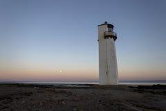 Sorgere della luna del faro di Southerness al tramonto Immagini Stock