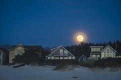 Sorgere della luna sopra le case di spiaggia Immagini Stock